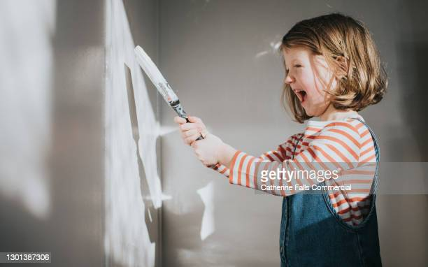 happy child painting a wall with white paint - decoration stock pictures, royalty-free photos & images