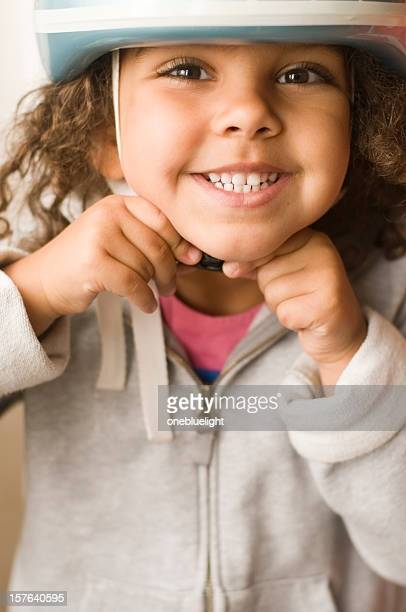 happy child (4-5) putting cycle helmet on, portrait - children only stock pictures, royalty-free photos & images