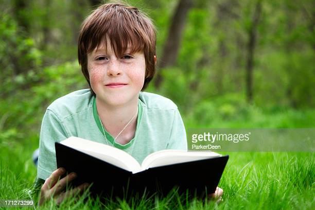 niño feliz leyendo un libro al aire libre en la naturaleza - 10 11 años fotografías e imágenes de stock