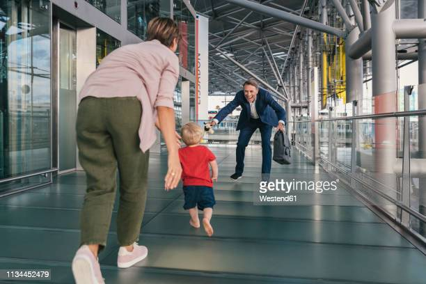 happy child running into arms of travelling businessman at the airport - arms outstretched stock pictures, royalty-free photos & images