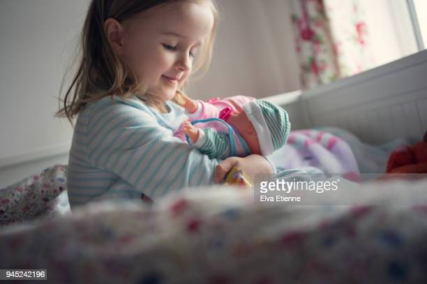 happy child sitting on a bed and playing with toy dolls - puppe stock-fotos und bilder