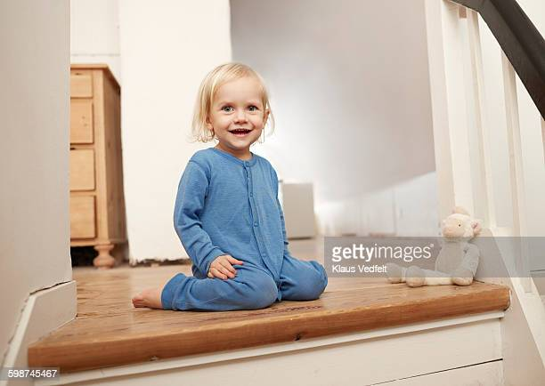 Happy child sitting on top of staircase