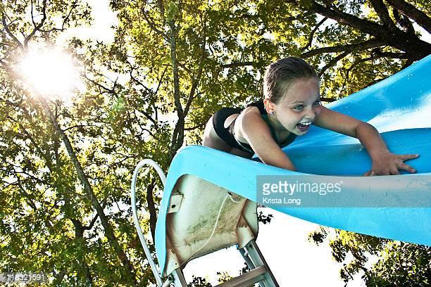 Happy child sliding into pool