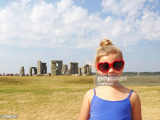 Happy child standing in front of Stonehenge
