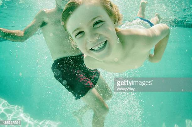 Happy child swimming with his grandpa underwater