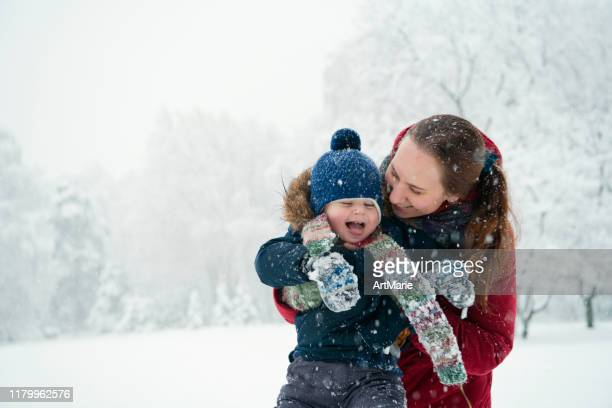 happy child trying to catch snowflakes in winter outdoors - warm clothing stock pictures, royalty-free photos & images