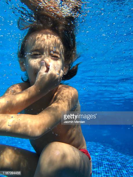happy child underwater in a swimming pool - 鼻をつまむ ストックフォトと画像