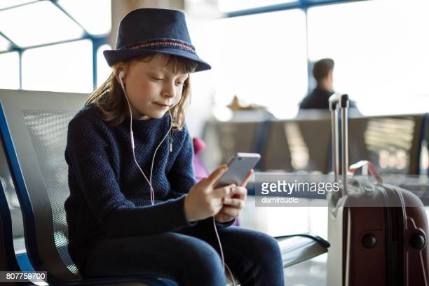 Happy child using smart phone at the airport
