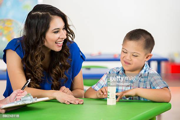 Happy child with Down Syndrome accomplishing task in school
