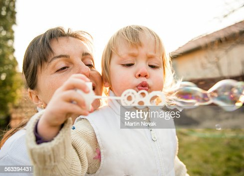 Happy childhood - mother and child blowing soap bu