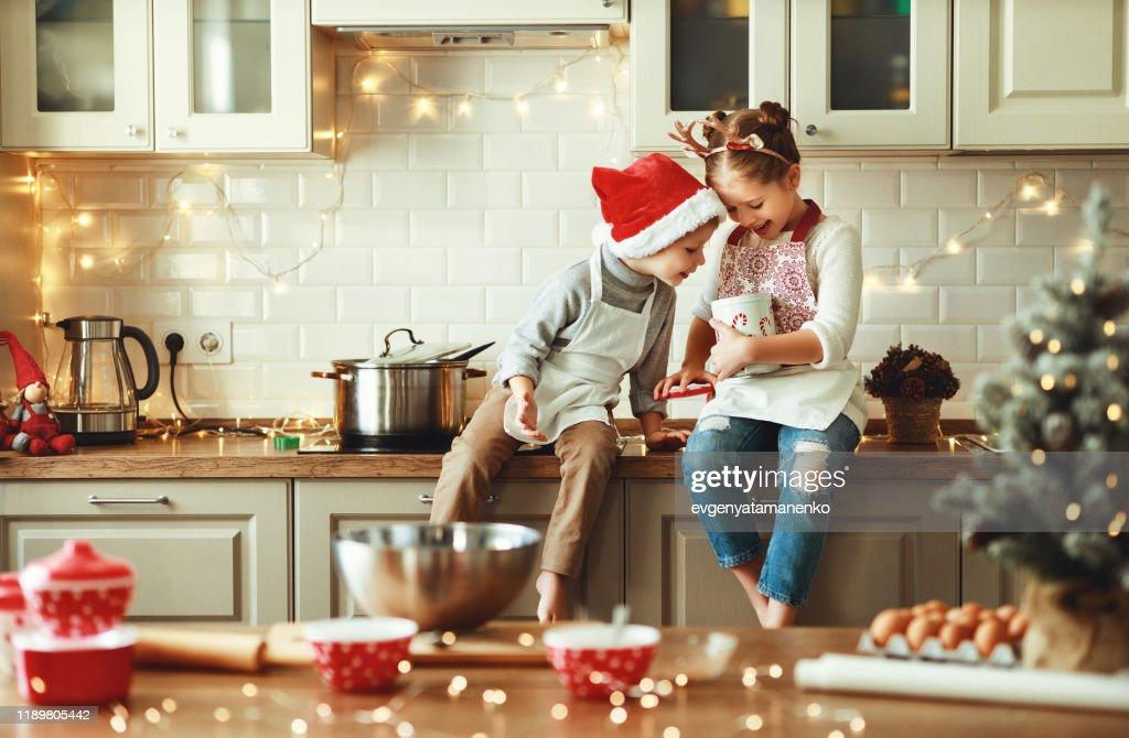 happy children boy and girl bake christmas cookies : Stock Photo