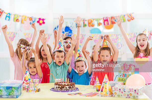 Happy children celebrating at birthday party looking at camera.