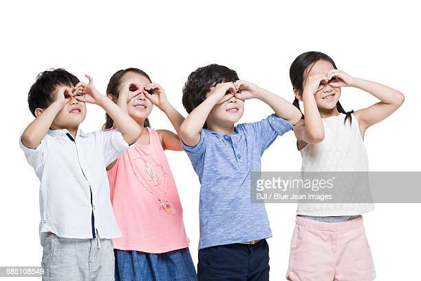 Happy children circling eyes with fingers