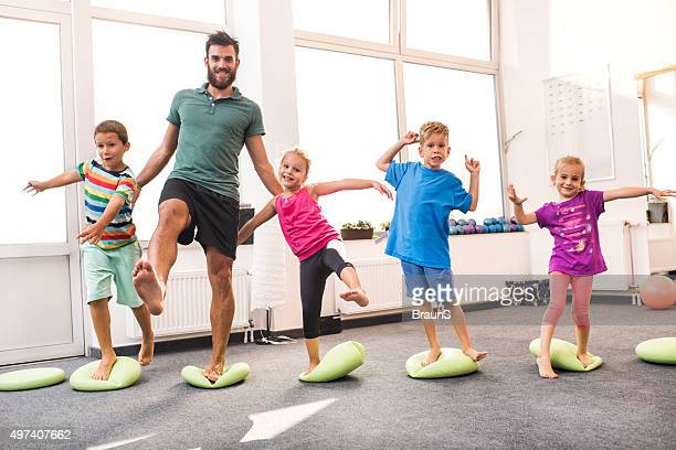 Happy children doing balance exercises with their coach.