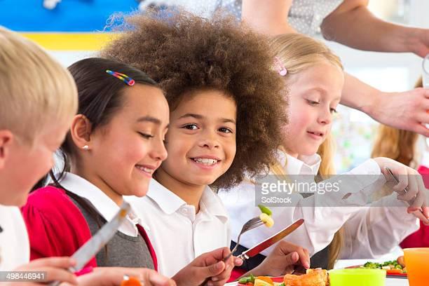 Happy children eating dinner at school