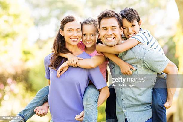 happy children enjoying piggyback ride on parents - vier personen stockfoto's en -beelden