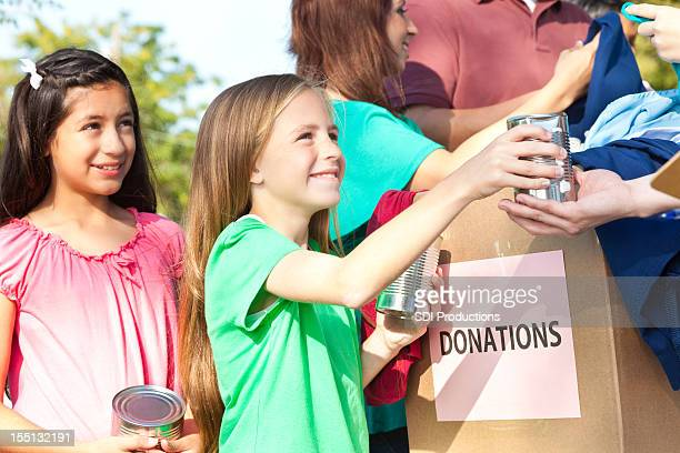 happy children handing donations in at a donation center - meals on wheels stock pictures, royalty-free photos & images