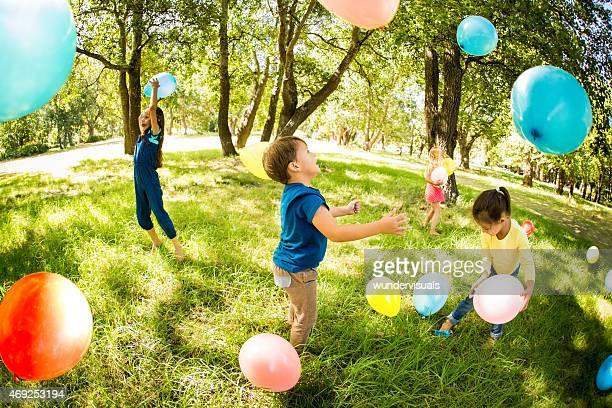 Des enfants heureux s'amuser dans un parc à montgolfières