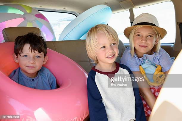 Happy children in car with beach gears for vacation