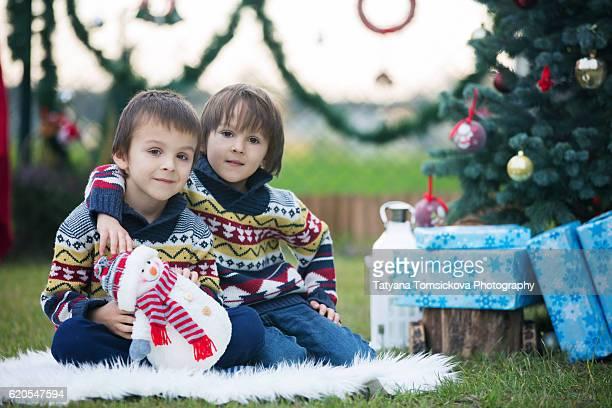 Happy children in front of the christmas tree outdoor in garden