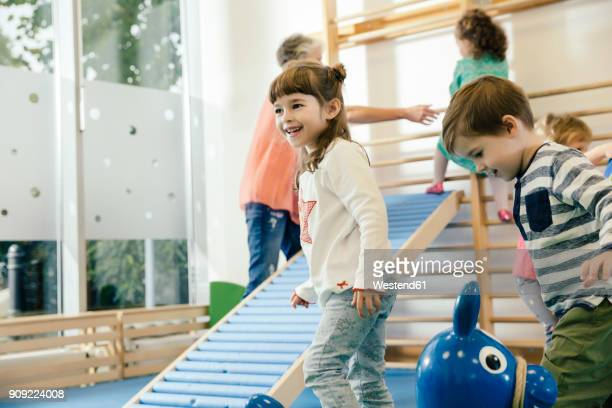happy children in gym room in kindergarten - kindergarten stock-fotos und bilder