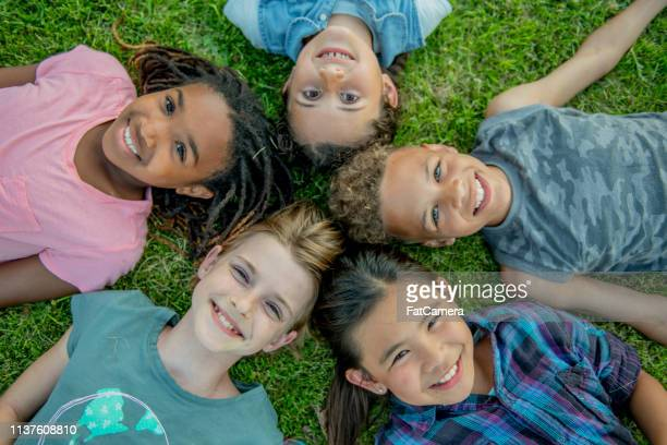 happy children lie on the grass with their heads touching - pre adolescent child stock pictures, royalty-free photos & images