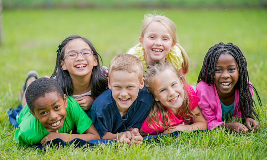 Happy children lying in the grass 1070887914