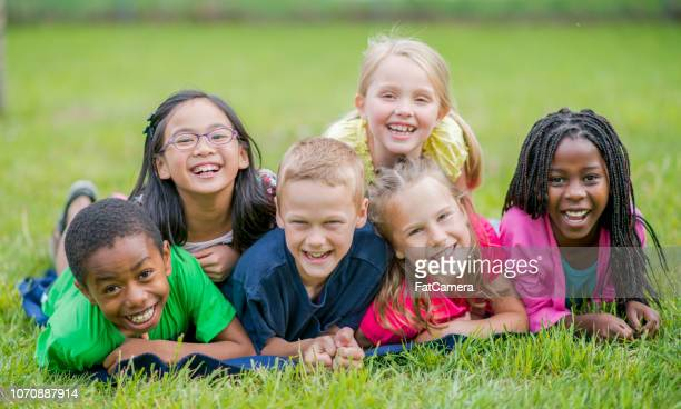 happy children lying in the grass - giochi per bambini foto e immagini stock