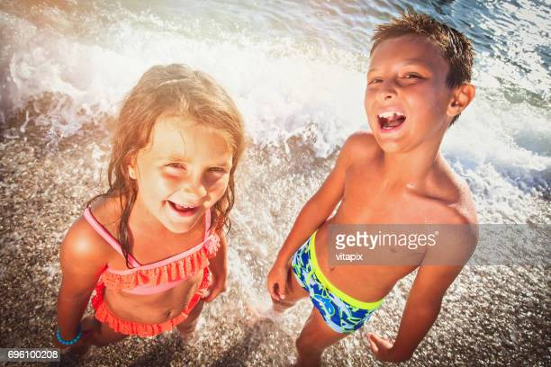 happy children on a summer vacation at the beach - girl sitting on boys face stock photos and pictures