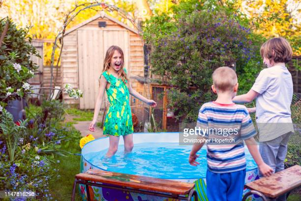 happy children playing in a paddling pool in a  garden - wet t shirt girls stock photos and pictures