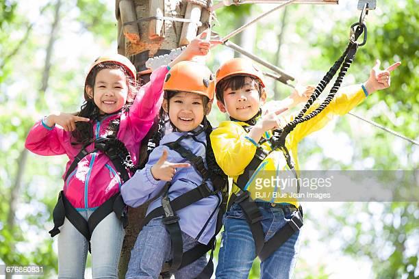 Happy children playing in tree top adventure park