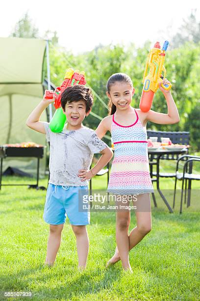 Happy children playing squirt guns