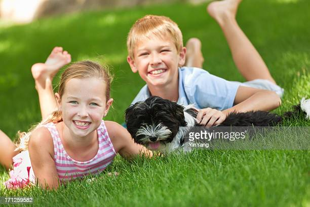 Happy Children Playing with Family Pet Dog in Backyard