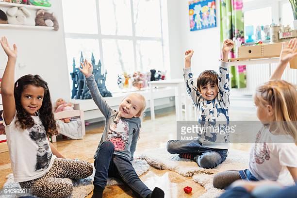 Happy children raising hands while sitting in preschool