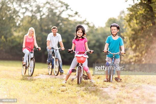 Happy children riding bikes with their parents in nature.