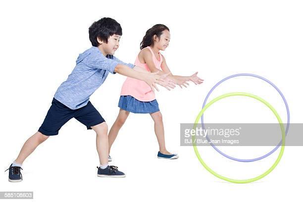 Happy children rolling plastic hoops