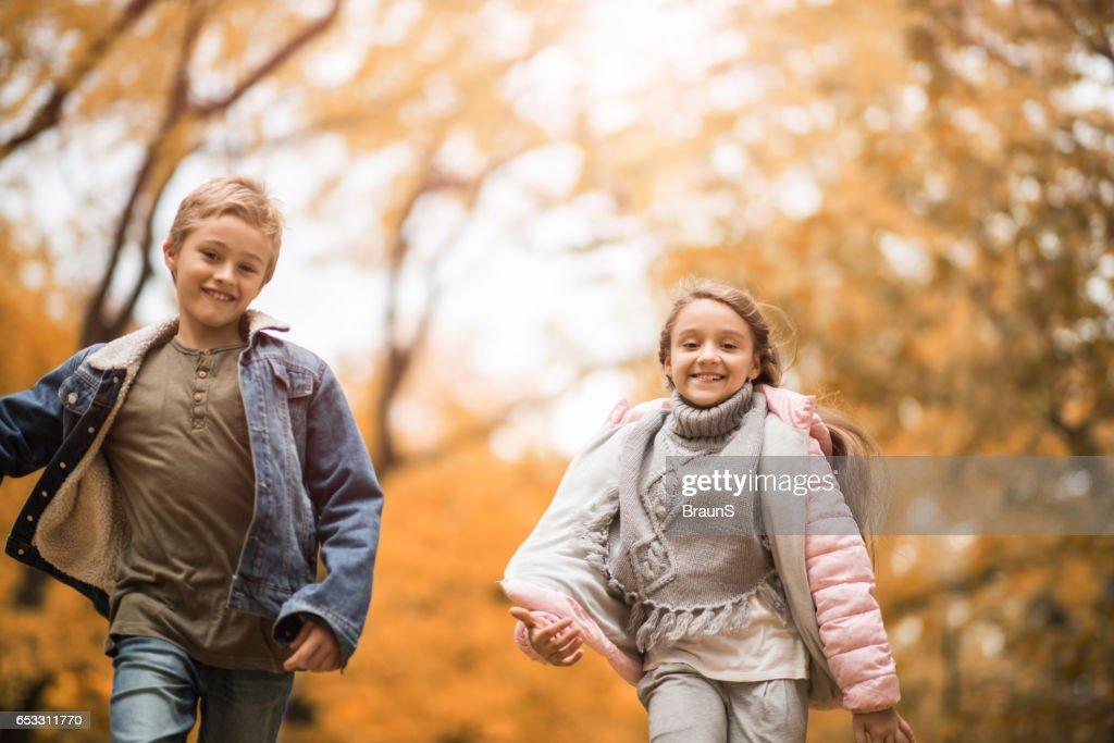 Gelukkige kinderen uitgevoerd in herfstdag in het park. : Stockfoto