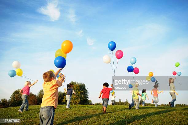 Happy children running in field with balloons