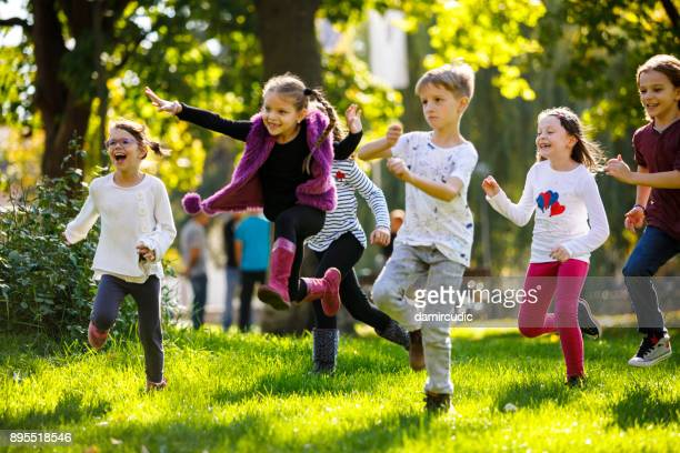 happy children running outside - offspring stock pictures, royalty-free photos & images