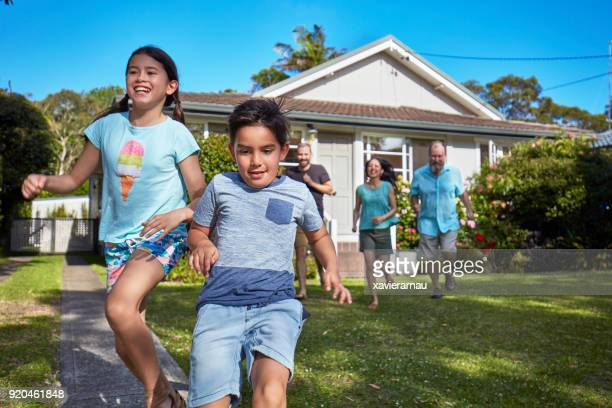 happy children running with family in lawn - sydney chase stock pictures, royalty-free photos & images