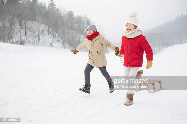 happy children running with sled on the snow - tobogganing ストックフォトと画像
