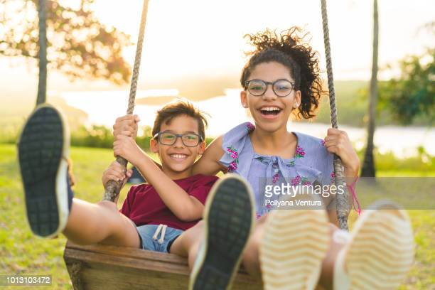 happy children swinging and smiling at golden sunset - pre adolescent child stock pictures, royalty-free photos & images