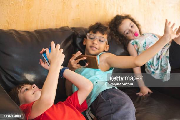 happy children using smart phones - two seater sofa stock pictures, royalty-free photos & images