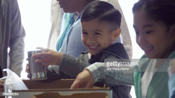 happy children volunteer in food bank - humanitarian aid stock pictures, royalty-free photos & images