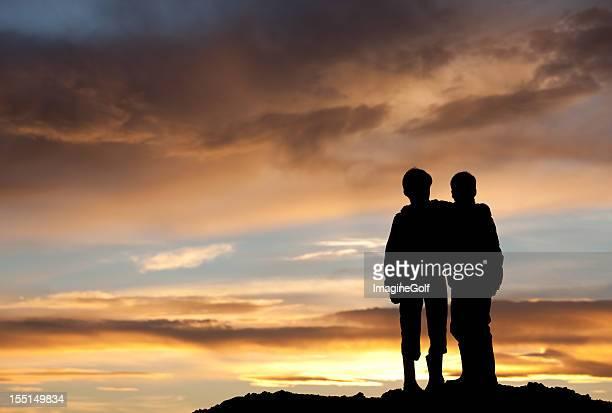 Enfants heureux en regardant le coucher de soleil