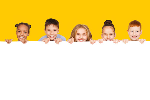 Happy children with empty board, yellow background 1172147023