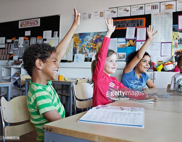Happy children with raised hands in school class