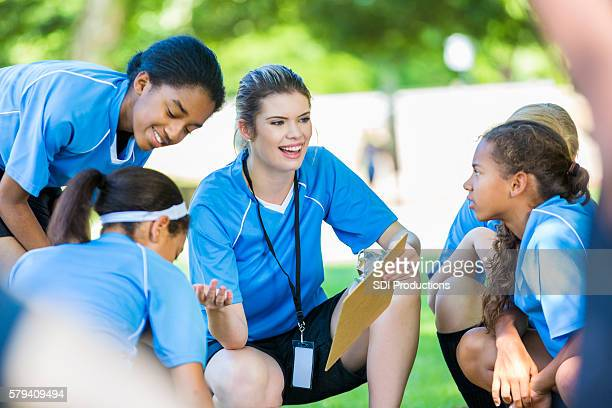 Happy childrens soccer coach huddled with players