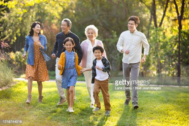 happy chinese family having fun in park - east asian ethnicity stock pictures, royalty-free photos & images