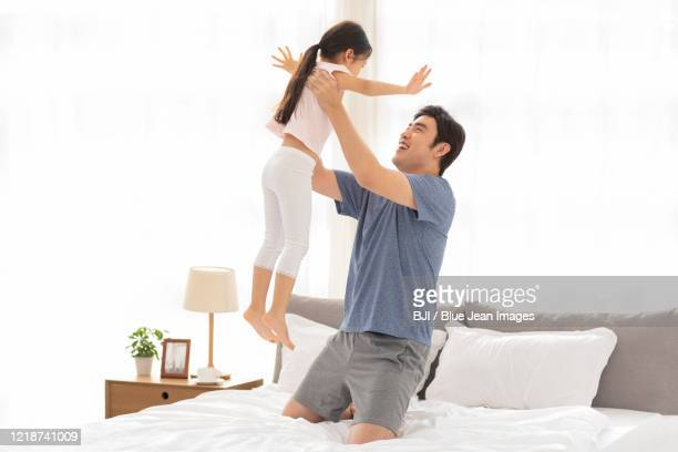 happy chinese father and daughter having fun in bedroom - girl wrestling stock pictures, royalty-free photos & images